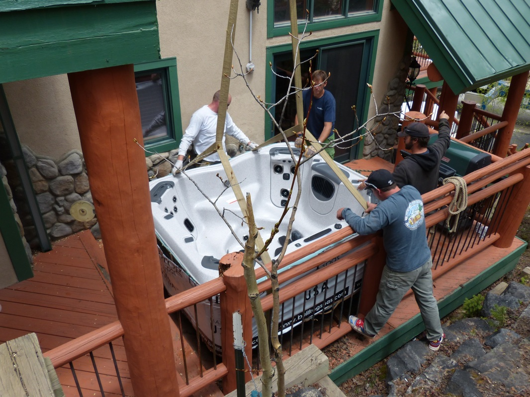 men installing hot tub on deck